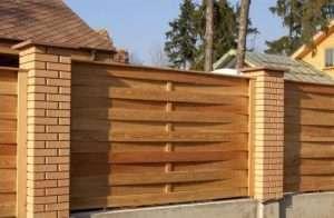 Деревянный забор на кирпичных опорах